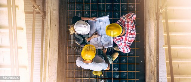 istock Female architect and two consruction workers on a construction site 810296690