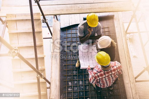 istock Female architect and two consruction workers on a construction site 810297312