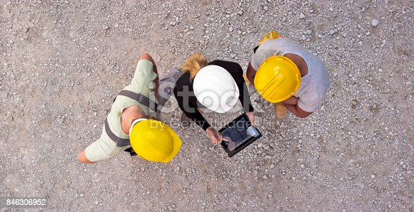 istock Female architect and two construction workers checking plan on digital tablet and pointing at building to check progress 846306952