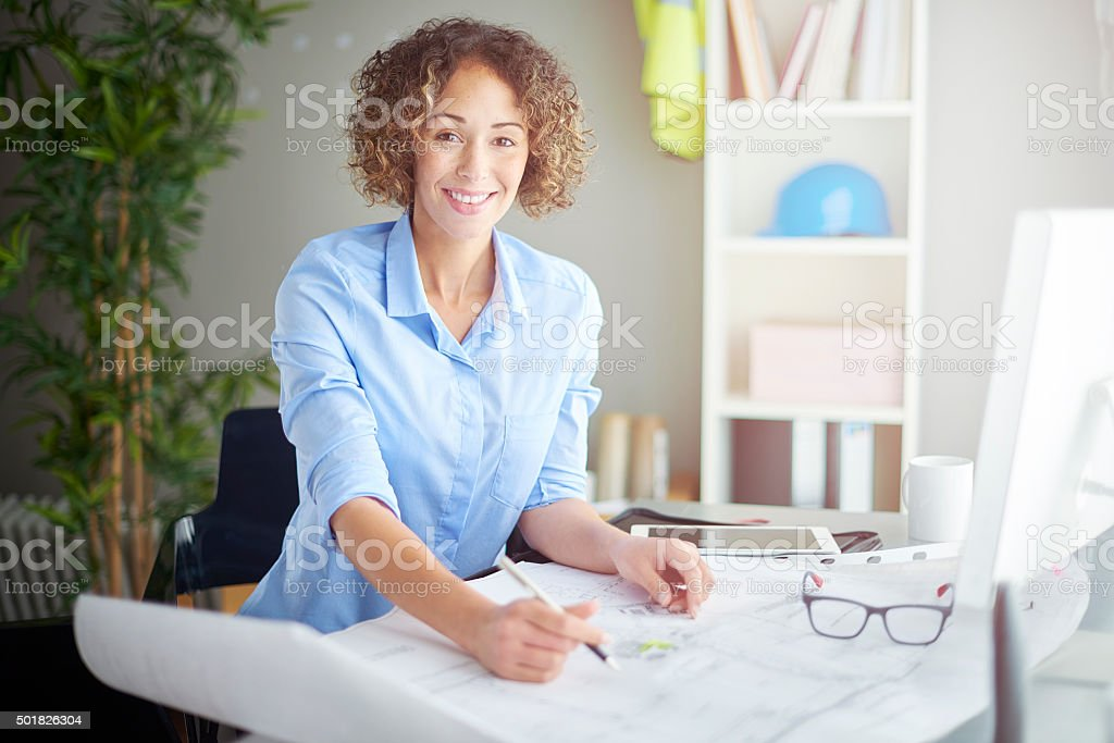 A female architect or building surveyor sits at her desk looking over...