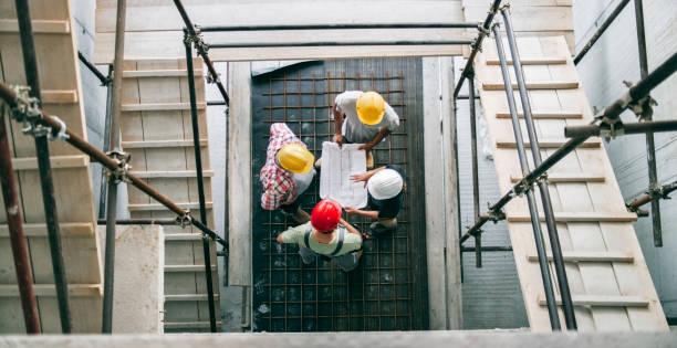 femme architecte expliquant les détails du plan au gestionnaire du site et foreman debout au bas de l'escalier de l'échafaudage - chef de projet photos et images de collection