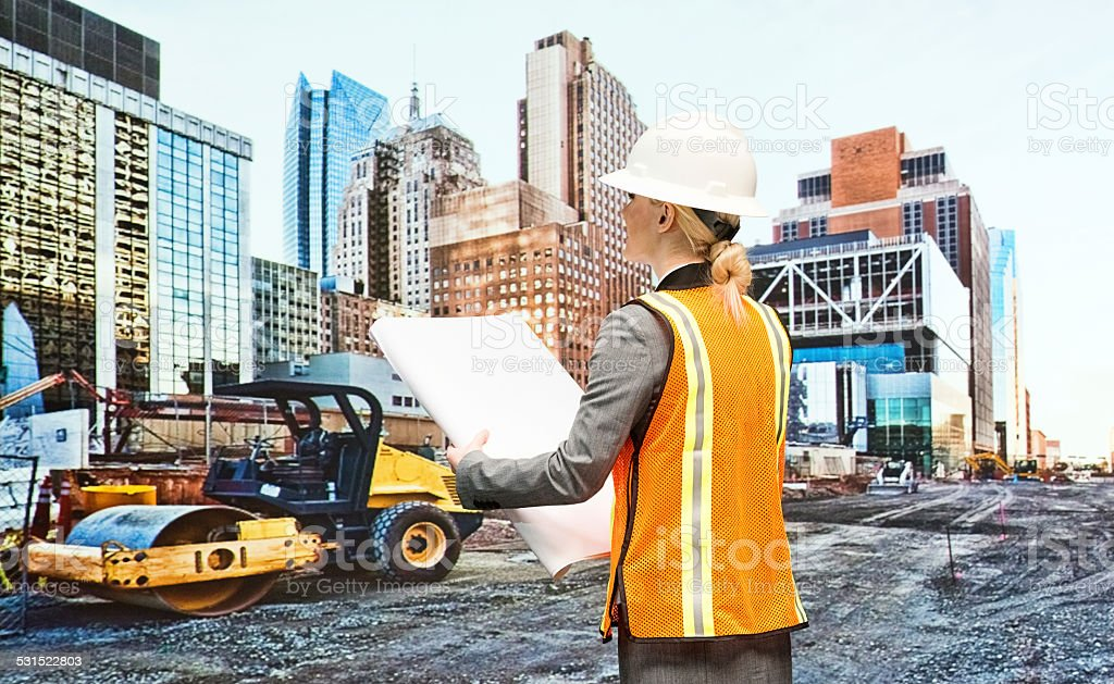 Female architect holding blueprint out in the city stock photo