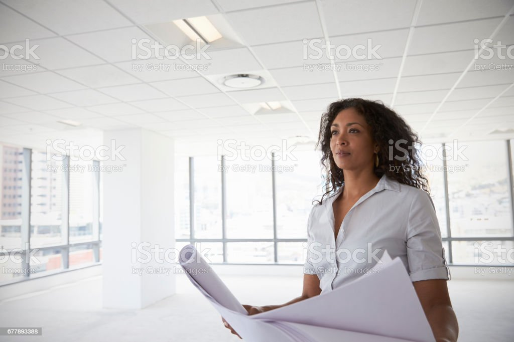 Female Architect In Modern Empty Office Looking At Plans stock photo