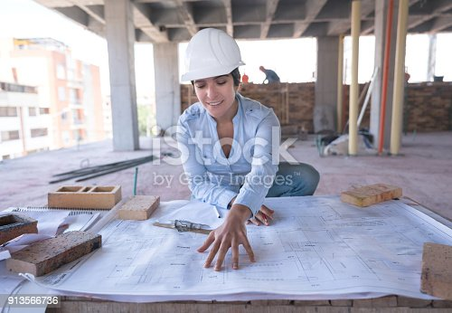 istock Female architect looking at a blueprint at a construction site 913566736