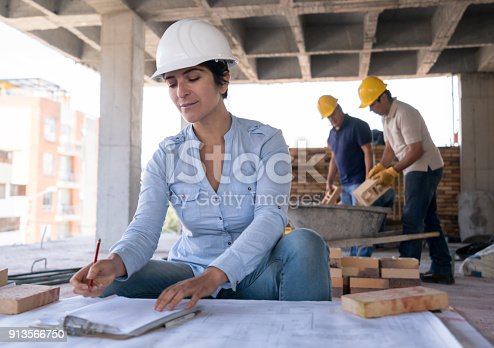 istock Female architect looking at a blueprint at a construction site 913566750