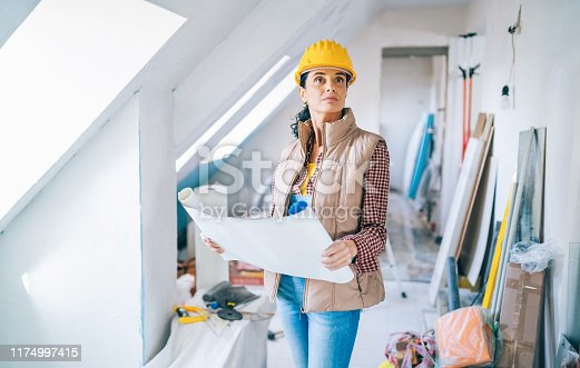 Female architect looking at blueprints on construction site