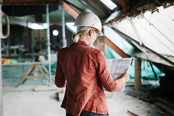 arquitecto looking over blueprints hembra - arquitecta fotografías e imágenes de stock