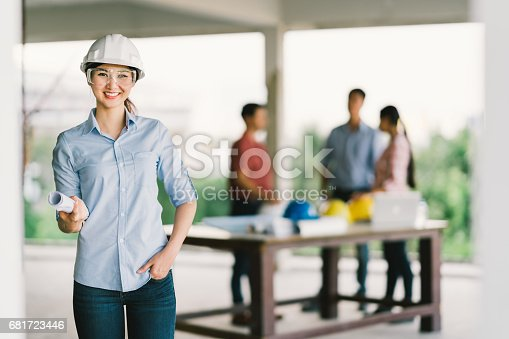 1166176793 istock photo Female architect or engineer with blueprint at building construction site. Coworker meeting on blur background. Industry, teamwork discussion, or job occupation concept 681723446