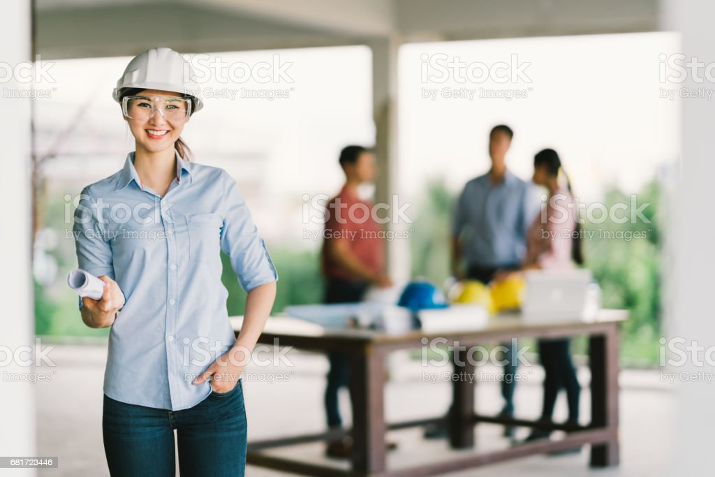 Female architect or engineer with blueprint at building construction site. Coworker meeting on blur background. Industry, teamwork discussion, or job occupation concept stock photo