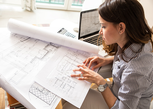 Female architect working at home.She looking at blueprint.