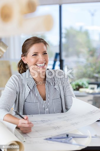 istock Female architect sits before a blueprint and smiles 823845680