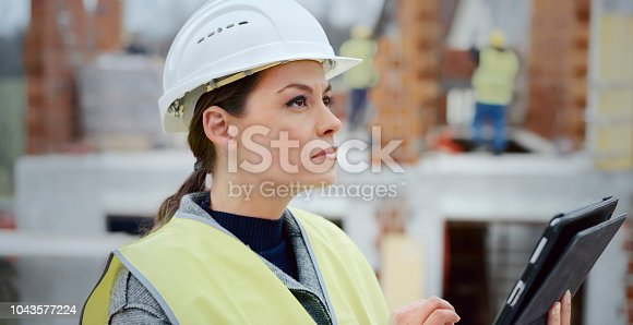 Female architect holding digital tablet and checking plans while standing in middle of construction site.