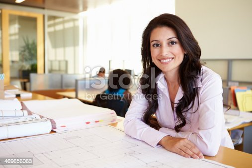 istock Female Architect Studying Plans In Office 469656063