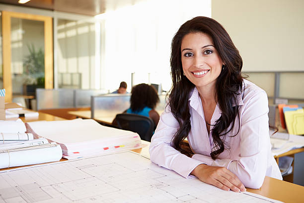 female architect studying plans in office - latina woman stock photos and pictures