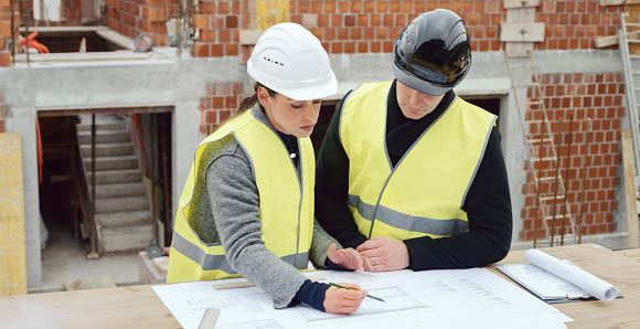 Female architect and male investor standing by table with plan on it at construction site and drawing details while discussing them.