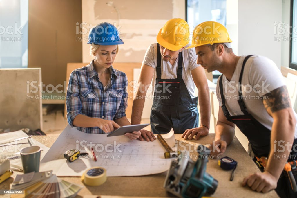 Female architect using digital tablet with two manual workers at construction site. stock photo