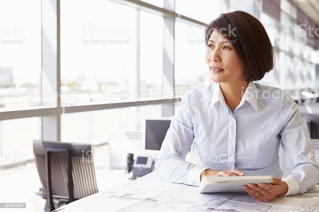 Female architect using tablet computer, looking away stock photo