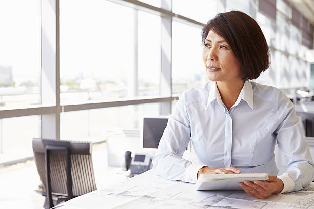 female architect using tablet computer, looking away - professional sport stock photos and pictures