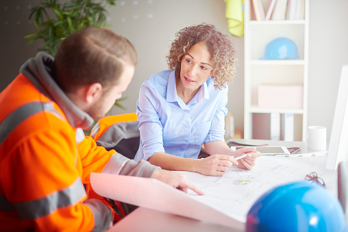 A female architect or site agent sits at her desk looking over some blueprints , whilst discussing the building project with her foreman .The foreman is wearing hi vis jacket , and their safety clothing is scattered about the office .