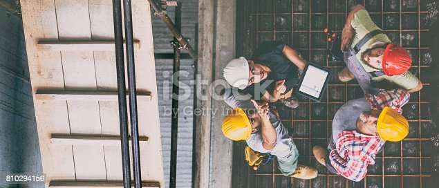 istock Female architect with three consruction workers on a construction site 810294156