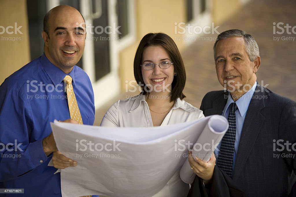 Female architect with two males holding architectural plans royalty-free stock photo