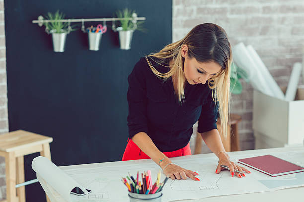 Female Architect Working In Her Office. Female architect working in her new modern office. Standing and examining blueprints for her new project. In front of her on the desk are pencils. interior designer stock pictures, royalty-free photos & images