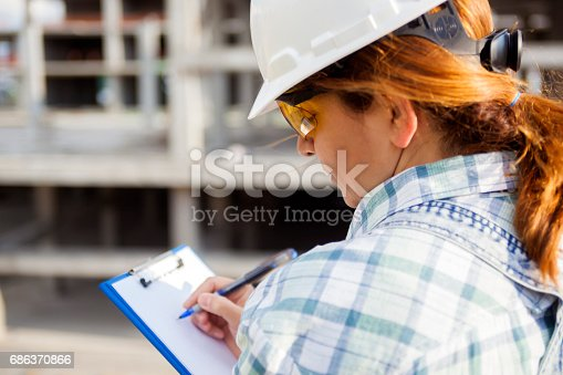 Female architect writing on clipboard at construction site