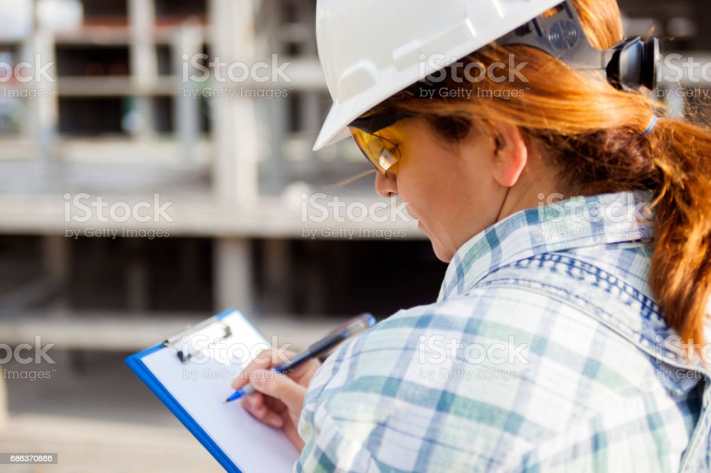 Female architect writing on clipboard at construction site stock photo