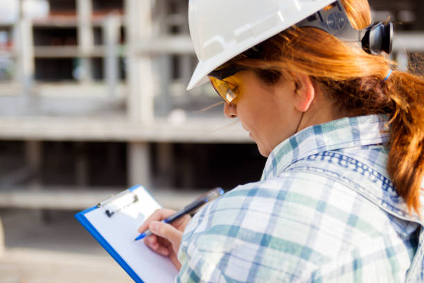 female architect writing on clipboard at construction site - clipboard stock photos and pictures