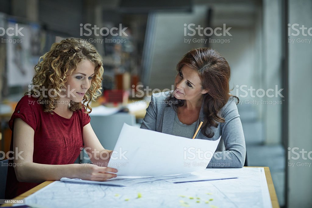 Female architect showing project to coworker in modern studio