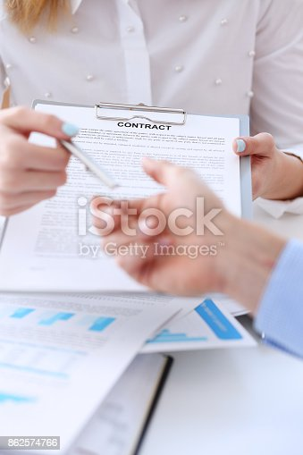 863148614istockphoto Female arm in suit offer contract form on clipboard pad 862574766