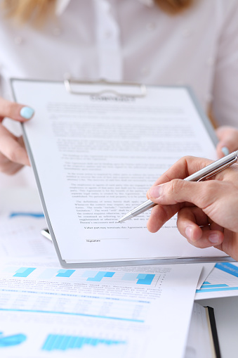 863148614 istock photo Female arm in suit offer contract form on clipboard pad 862574802