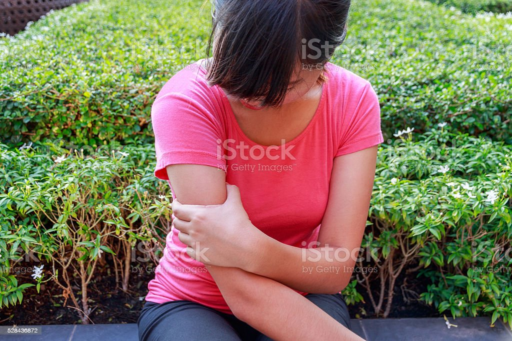 Female arm pain sitting in the park stock photo