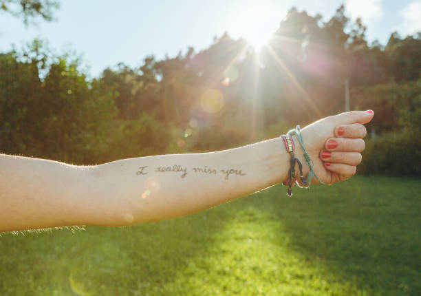 Female arm with text -I really miss you- written in skin stock photo