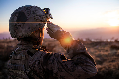 Female Army Solider Saluting against sunset sky