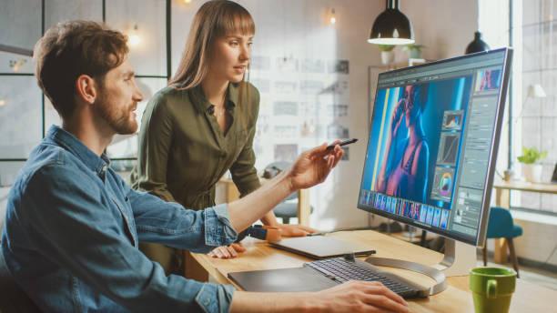 Female Art Director Consults Designer Colleague, Sie arbeiten an einem Portrait in Fotobearbeitungssoftware. Sie arbeiten in einem coolen Büro Loft. Sie sehen sehr kreativ und cool aus. – Foto