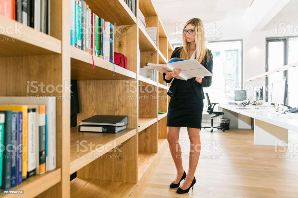 Female Art Director Designer reading Book for inspiration in modern office library stock photo