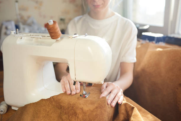 weiblichen handwerker, die leder nähmaschine einfädeln - diy leder stock-fotos und bilder