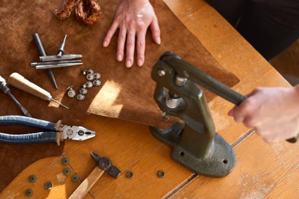 weiblichen handwerker arbeiten an manuellen vintage maschine für leder umgeben mit werkzeugen - diy leder stock-fotos und bilder