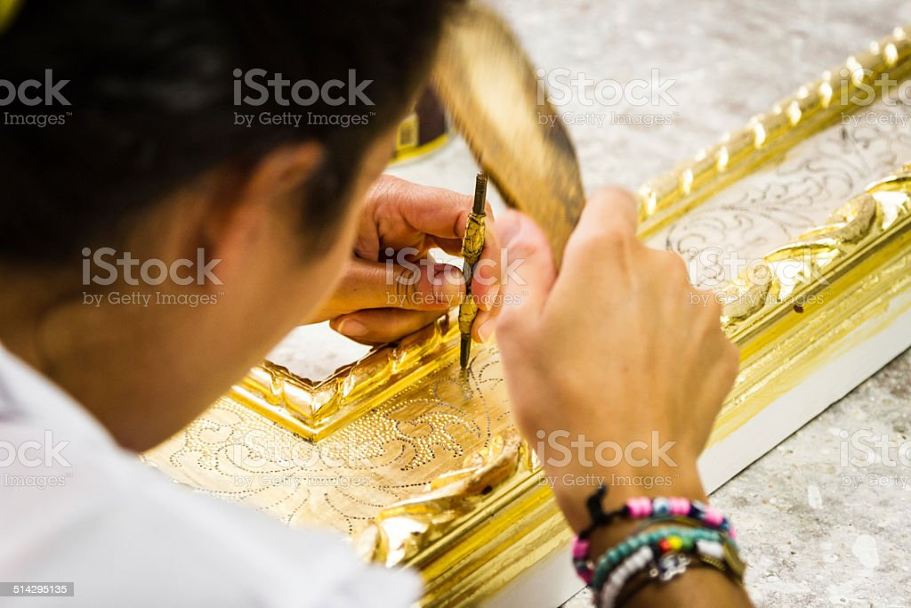 Female artist chiseling a wooden picture frame. stock photo