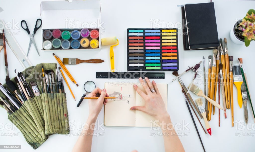 Female artist drawing graphic sketch at sketchbook with pencil in art gallery, her workplace. Top view photo of artistic tools lying on work-table: gouache, crayons palette and paintbrush collection. 免版稅 stock photo