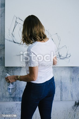 Female painter drawing with charcoal on canvas, preparatory drawings