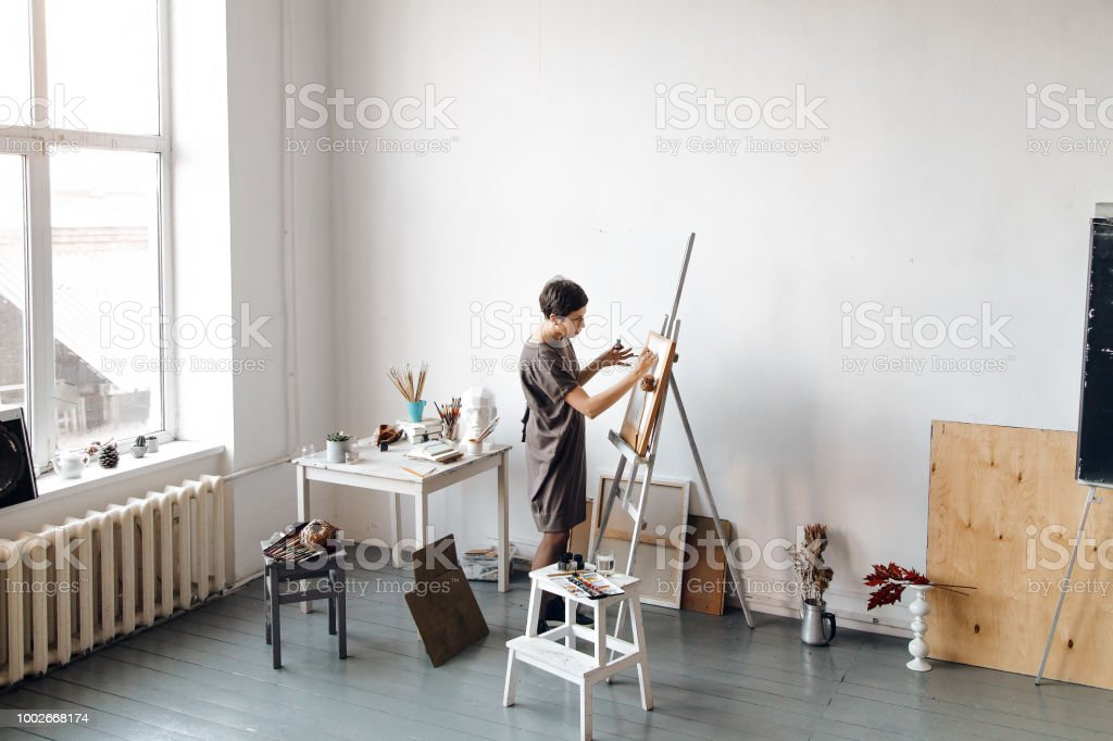 Female artist in her spacious white studio working with watercolor painting.  Natural lighting. Disclosure of creativity concept. Horizontal composition with copy space. stock photo