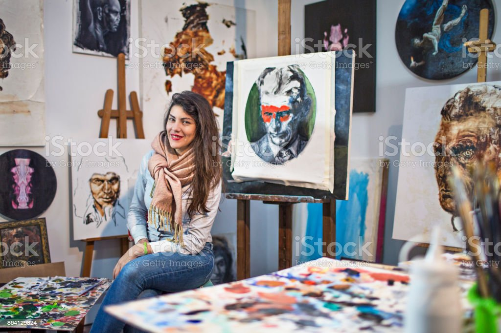 Female artist in her studio surrounded by her painting art royalty-free stock photo