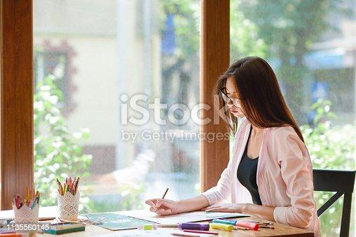 istock Female artist sitting, holding pencil, painting. 1135560145