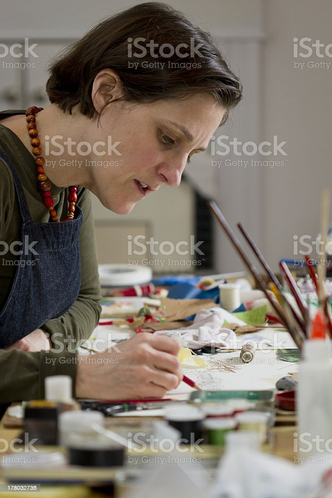 Female artist sketching on paper using pencil royalty-free stock photo