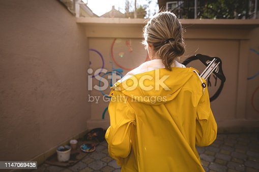 Artistic girl in a yellow raincoat painting a wall.