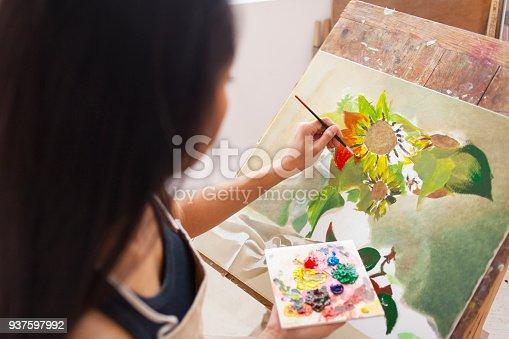 istock Female artist working in studio 937597992