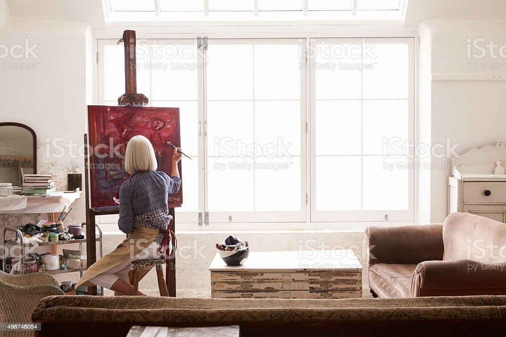 Female Artist Working On Painting In Bright Daylight Studio stock photo