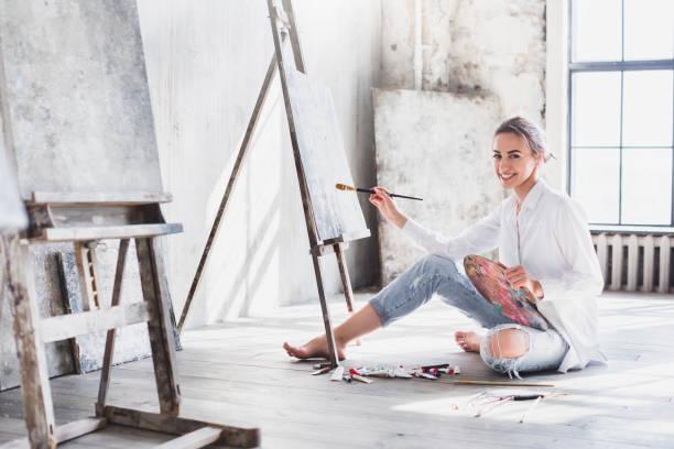 Female artist working on painting In bright daylight studio. stock photo